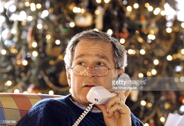 S President George W Bush speaks with members of the US armed forces via telephone December 24 2002 at the presidential retreat Camp David in...