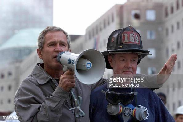 President George W Bush standing next to retired firefighter Bob Beckwith speaks to volunteers and firemen as he surveys the damage at the site of...