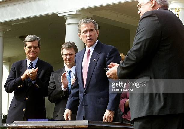 President George W Bush stands after signing the Job Creation and Worker Assistance Act of 2002 during a live broadcast of his weekly radio address...