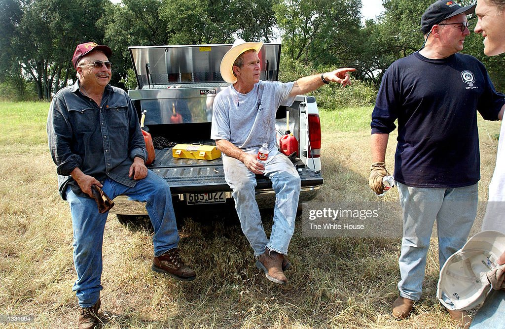U.S. President George W. Bush takes a break from cedar clearing at his ranch August 9, 2002 in Crawford,Texas. Also pictured are (from L)friend Ken Englebrecht, Deputy Chief of Staff Joe Hagin and White House staffer Reed Dickens. Bush is working from his 1,600-acre ranch in Texas for about a month.