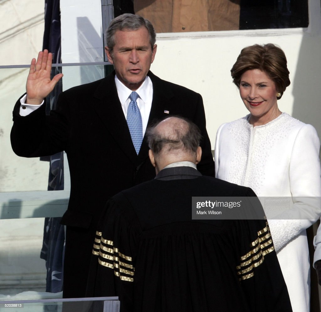 U.S. President George W. Bush takes the oath of office from U.S. Suprme Court Chief Justice William Rehnquist (C) during inaugural ceremonies while first lady Laura Bush looks on January 20, 2005 in Washington, D.C. U.S. President George W. Bush is being sworn in for a second term.
