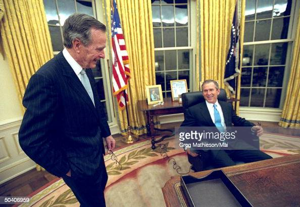 President George W Bush talking w his father former President George HW Bush while sitting at his desk in the Oval Office of the White House for the...