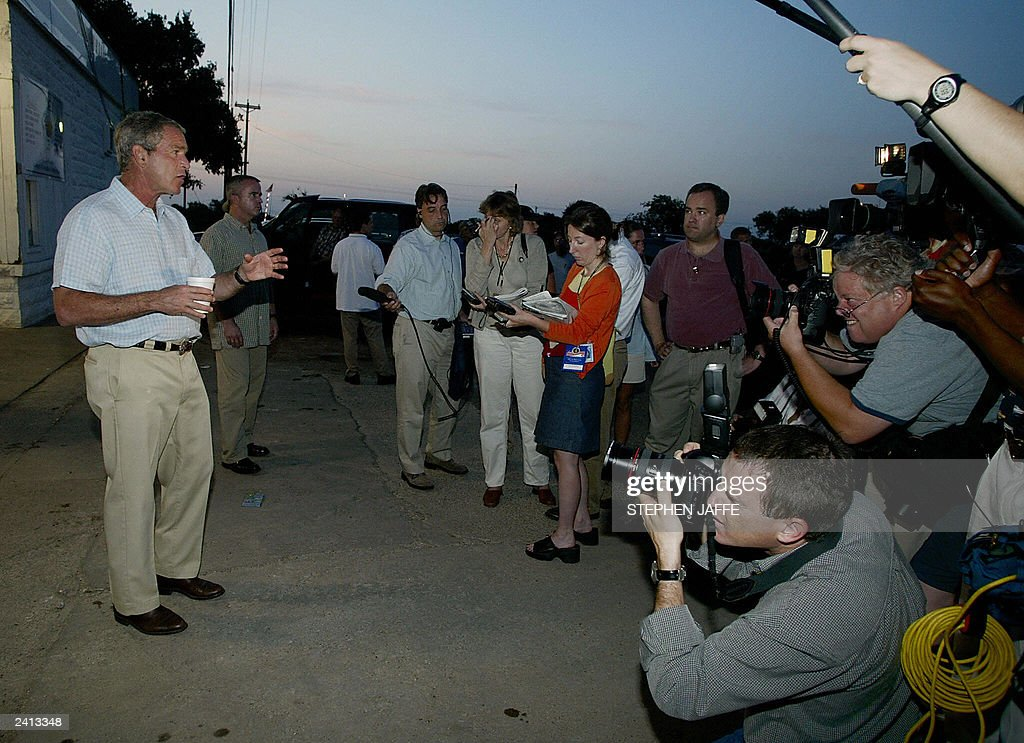 US President George W Bush talks to the media after getting an early morning cup of coffee from a downtown Crawford coffee shop enroute to play golf...