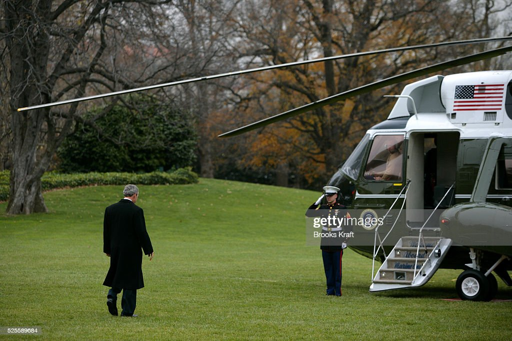 US President George W Bush walks across the South Lawn of the White House to board Marine One helicopter December 5 2005