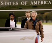 President George W Bush walks to his pickup truck with British Prime Minister Tony Blair and National Security Advisor Condoleezza Rice as Blair...