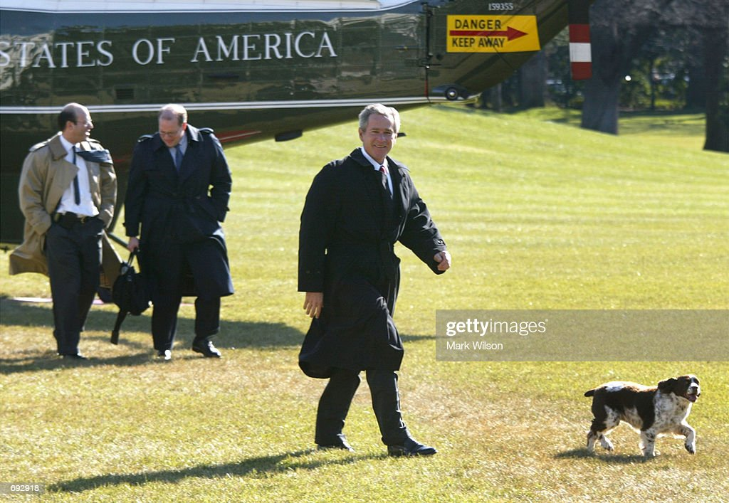 U.S. President George W. Bush walks with his dog Spot followed by Press Secretary Ari Fleischer and Deputy Cheif of Staff Joe Hagin after getting off Marine One January 11, 2002 on the South Lawn of the White House in Washington, DC. The president was returning from a trip to Pennsylvania where he signed legislation to clean up thousands of polluted industrial sites.