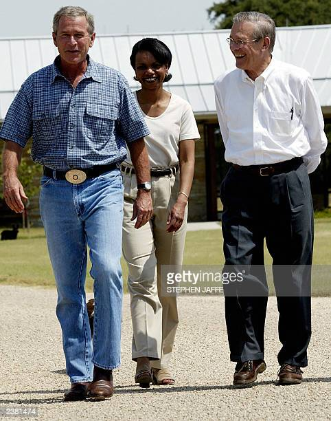 US President George W Bush walks with National Security Advisor Condoleezza Rice and Secretary of Defense Donald Rumsfeld at the President's ranch in...