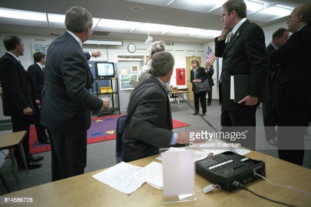 President George W Bush watches television coverage of the attacks on the World Trade Center Tuesday Sept 11 during a briefing in a classroom at Emma...