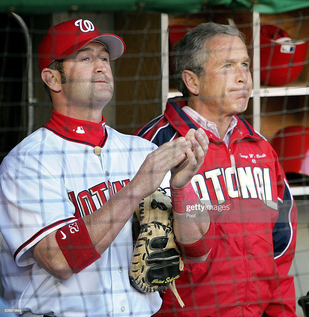 US President George W Bush watches the pregame show with catcher Brian Schneider of the Washigton Nationals prior to throwing out the first pitch for...