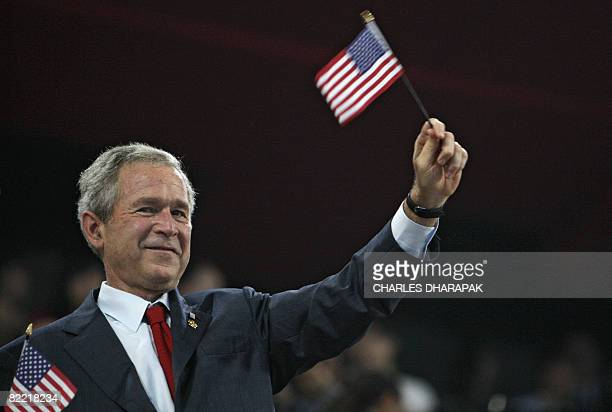 US President George W Bush waves a US flag as he watches the delegations arrive during the opening ceremony of the 2008 Beijing Olympic Games in the...