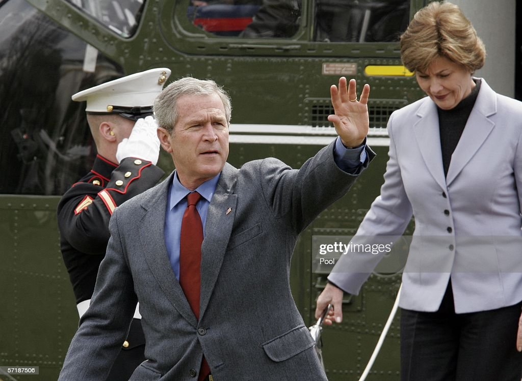 U.S. President George W. Bush waves as he and his wife, first lady Laura Bush, depart from Marine One as they arrive at the White House March 26, 2006 in Washington, DC. President Bush spent his weekend at Camp David.