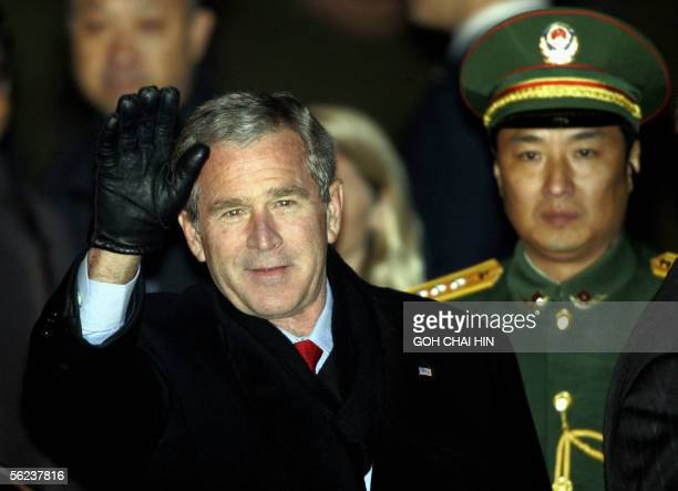 President George W Bush waves as he is accompanied by a Chinese People's Liberation Army officer on arrival at the Beijing Capital International...