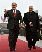 US President George W Bush waves as he walks alongside Palestinian leader Mahmud Abbas during a ceremony at the Muqataa the Palestinian Authority...