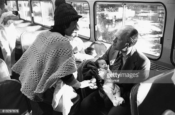 President Gerald Ford holds a Vietnamese baby on an Air Force bus after greeting refugees in California