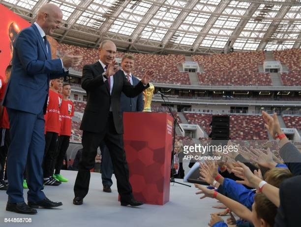 President Gianni Infantino and Russian President Vladimir Putin smile during the opening of the trophy tour ceremony at Luzhniki stadium in Moscow on...