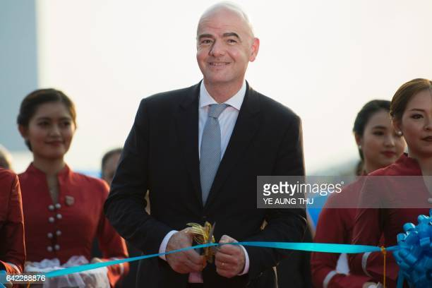 FIFA president Gianni Infantino cuts the ribbon as part of a ceremony to open the national football academy in Yangon on February 17 2017 The opening...