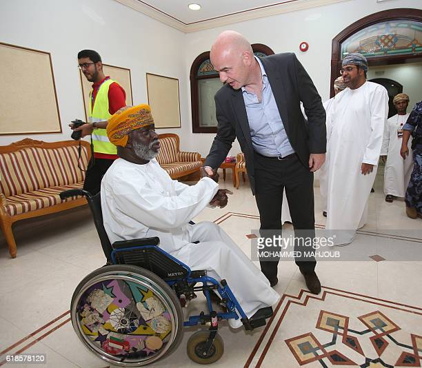 FIFA president Gianni Infantino greets a member of alShabab football club before the start of the Omani league football match between alShabab and...
