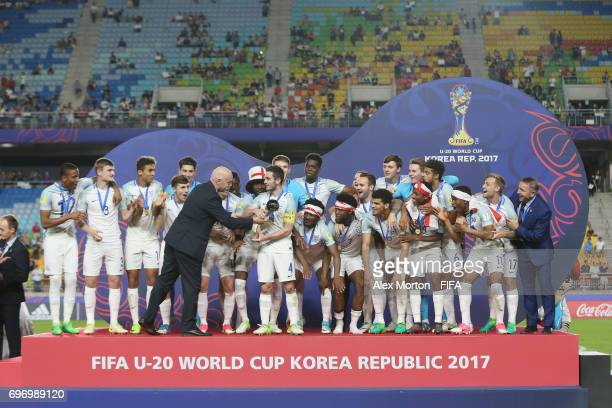 President Gianni Infantino hands the trophy to England captain Lewis Cook during the FIFA U20 World Cup Korea Republic 2017 Final match between...