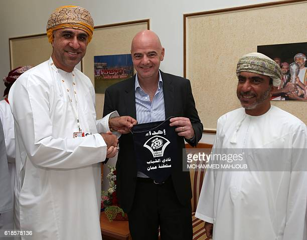 FIFA president Gianni Infantino poses with a Tshirt next to chairman of the Oman Football Association Salem bin Said alWahaibi and the president of...