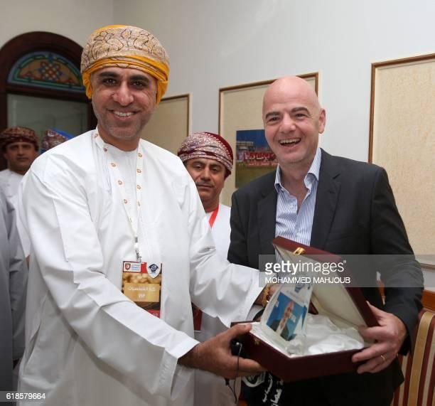 FIFA president Gianni Infantino receives a present from the president of the alShabab Omani football club Sheikh Hamza Abdulraheem alBalushi before...