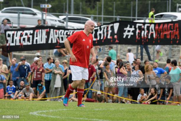 President Gianni Infantino walks past a banner deployed by activist against FIFA during 'The Gianni's game the match of legends' a football match...
