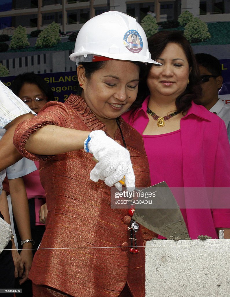 President Gloria Arroyo tops cement on a concrete block during a construction of a school building in Caloocan city suburban Manila on February 25...