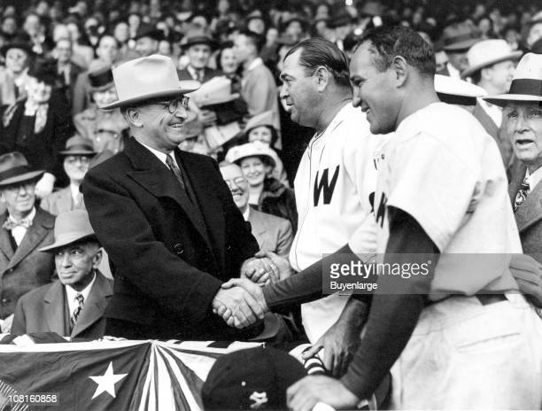 President Harry Truman shakes hands with Washington Senators manager Ossie Bluege and New York Yankees manager Bucky Harris while attending opening...
