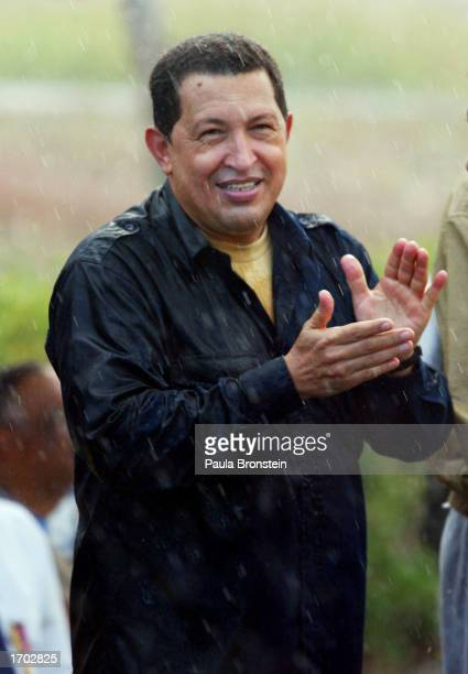 President Hugo Chavez applauds in the rain at a fuel distribution plant located 93 miles east of Caracas December 27 2002 in Carenero Venezuela...