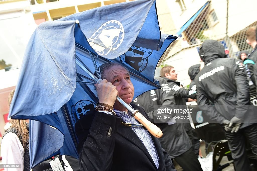 FIA president Jean Todt holds an umbrella on the grid at the Monaco street circuit, on May 29, 2016 in Monaco, ahead of the Monaco Formula 1 Grand Prix. / AFP / ANDREJ