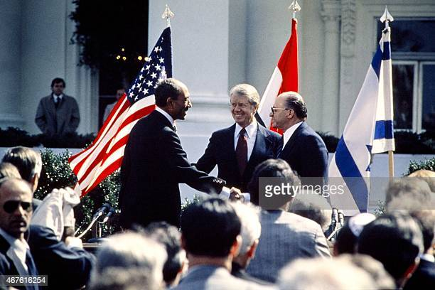 US President Jimmy Carter congratulates Egyptian President Anwar alSadat and Israeli Premier Menachem Begin as they shake hands on March 26 1979 on...
