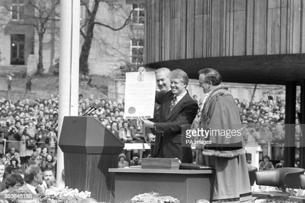 President Jimmy Carter holds up a scroll presented to him by the Lord Mayor of Newcastle Councillor Hugh White during a ceremony outside the city's...
