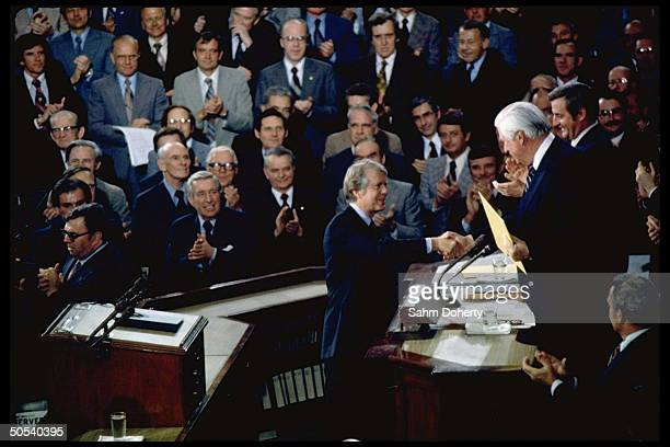 President Jimmy Carter shaking hands with Speaker of the House Tip O'Neill after delivering energy address to joint session of Congress as Robert...