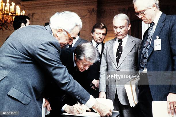 US President Jimmy Carter signs the order blocking Iranian funds in US banks on November 14 1979 in Washington DC as White House Counsel Lloyd Cutler...
