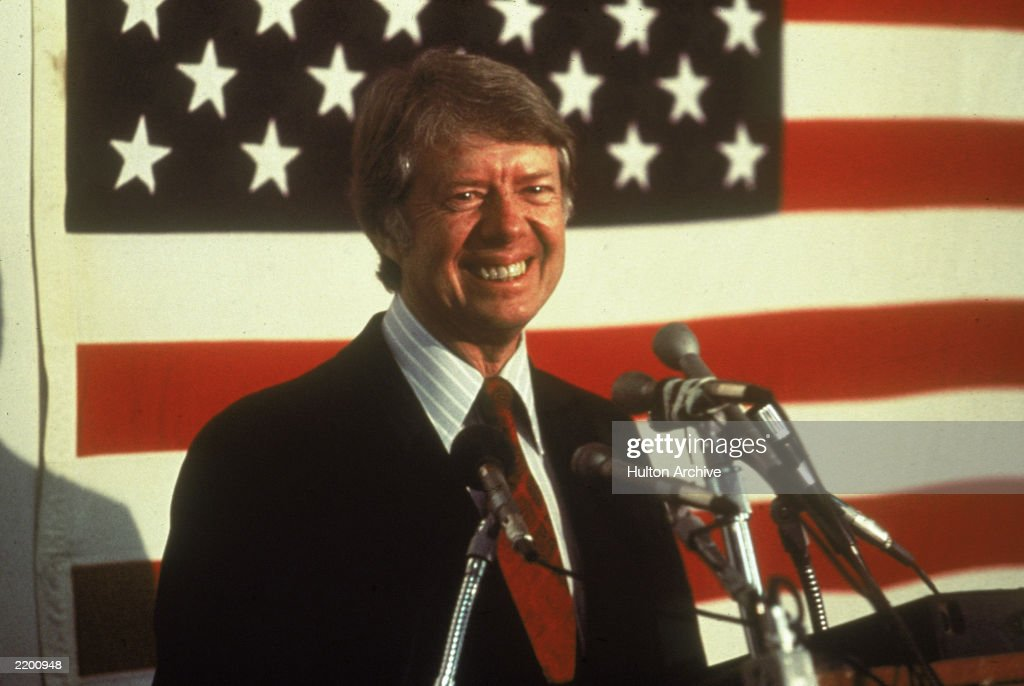 U.S. president <a gi-track='captionPersonalityLinkClicked' href=/galleries/search?phrase=Jimmy+Carter+-+US+President&family=editorial&specificpeople=93589 ng-click='$event.stopPropagation()'>Jimmy Carter</a> smiling at a podium in front of an American flag, 1970s.