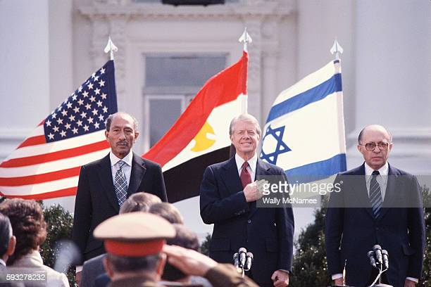 President Jimmy Carter with Egyptian President Anwar Sadat and Israeli Prime Minister Menachem Begin stand during the playing of national anthems on...