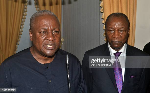 President John Dramani Mahama of Ghana and ECOWAS chairman speaks to the press as President Alpha Conde of Guinea listens on upon Mahama's arrival at...