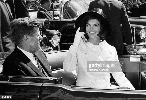 President John F Kennedy and First Lady Jacqueline Kennedy ride in a parade March 27 1963 in Washington DC