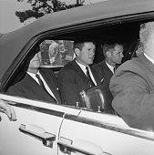 President John F Kennedy and his brothers Senator Edward Kennedy and Attorney General Robert Kennedy ride in the back of a car after visiting...