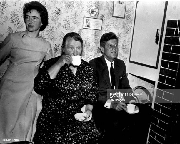 President John F Kennedy of America sits beside the fire to have a cup of tea with his hostess and second cousin Mrs Mary Ryan during his visit to...