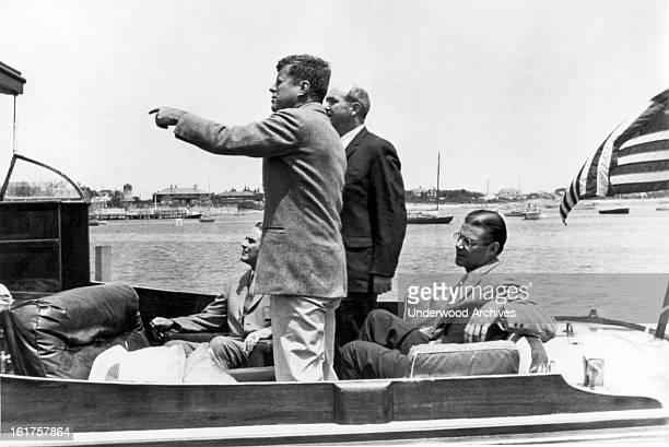 President John F Kennedy points out Hyannis Port landmarks to General Maxwell Taylor Secretary of State Dean Rusk and Secretary of Defense Robert...