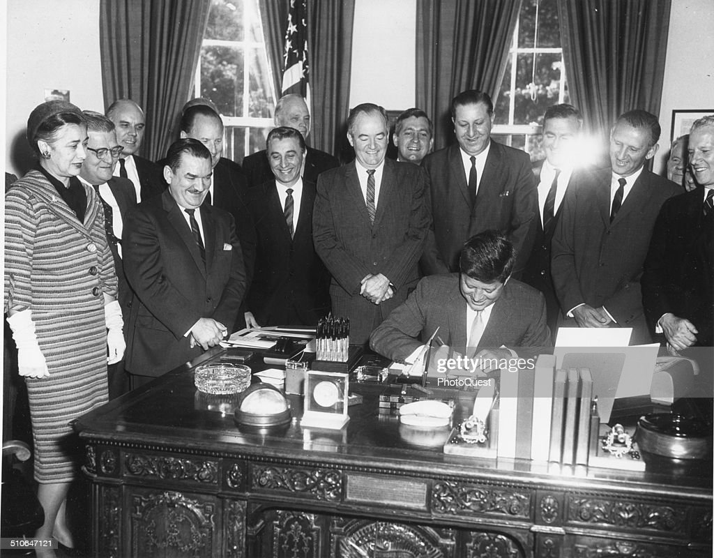 President John F Kennedy signs the Peace Corps Bill in the White House, Washington DC, 1961.