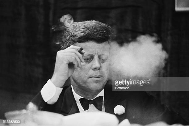 President John F Kennedy smokes a cigar during a Democratic fundraising dinner at the Commonwealth Armory at Boston University
