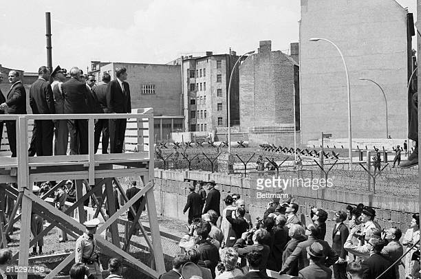 President John F Kennedy stands on a platform overlooking the Berlin Wall during his visit to West Berlin
