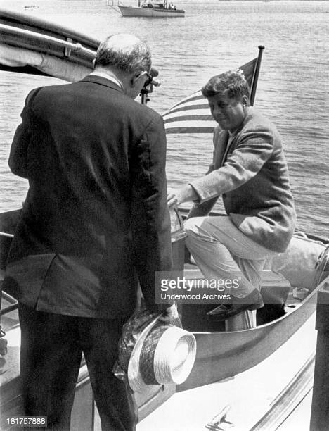President John F Kennedy steps into the cockpit of the yacht 'Marlin' as Secretary of State Dean Rusk walks aft Hyannis Port Massachusetts July 8 1961
