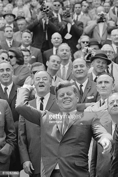 President John F Kennedy throws out the ceremonial first pitch to open the Washington Senators' 1963 season Behind him left to right are Senator...