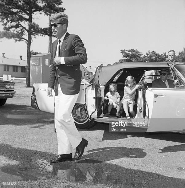 President John F Kennedy walks out of a car with his children Caroline and John Jr following him toward a hospital where they are visiting his wife...