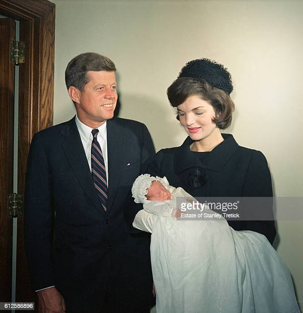President John F Kennedy with wife Jaqueline holding her son John Jr just after his christening at the Georgeown University Hospital Chapel His gown...