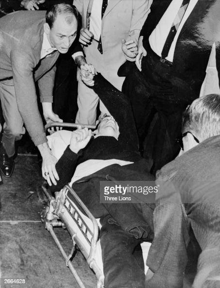President John F Kennedy's alleged assassin Lee Harvey Oswald is hurried into an ambulance after being shot at Dallas City Prison by night club owner...