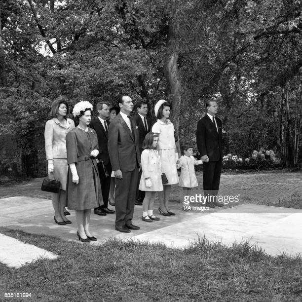 President John F Kennedy's children Caroline and John whose hand is held by the Duke of Edinburgh stand with other members of the party in silence...
