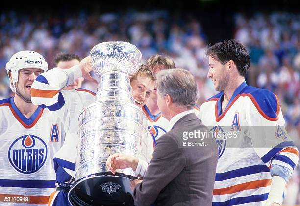 President John Ziegler presents Wayne Gretzky Mark Messier and Kevin Lowe of the Edmonton Oilers the Stanley Cup Trophy after the Oilers Game 4 win...